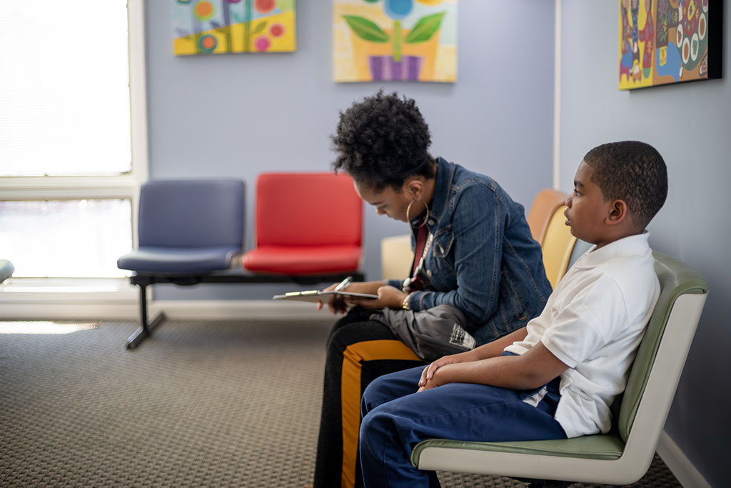 pediatric services - parent filling out paperwork in waiting room